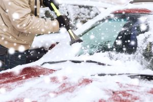 closeup of man cleaning snow from car windshield with brush